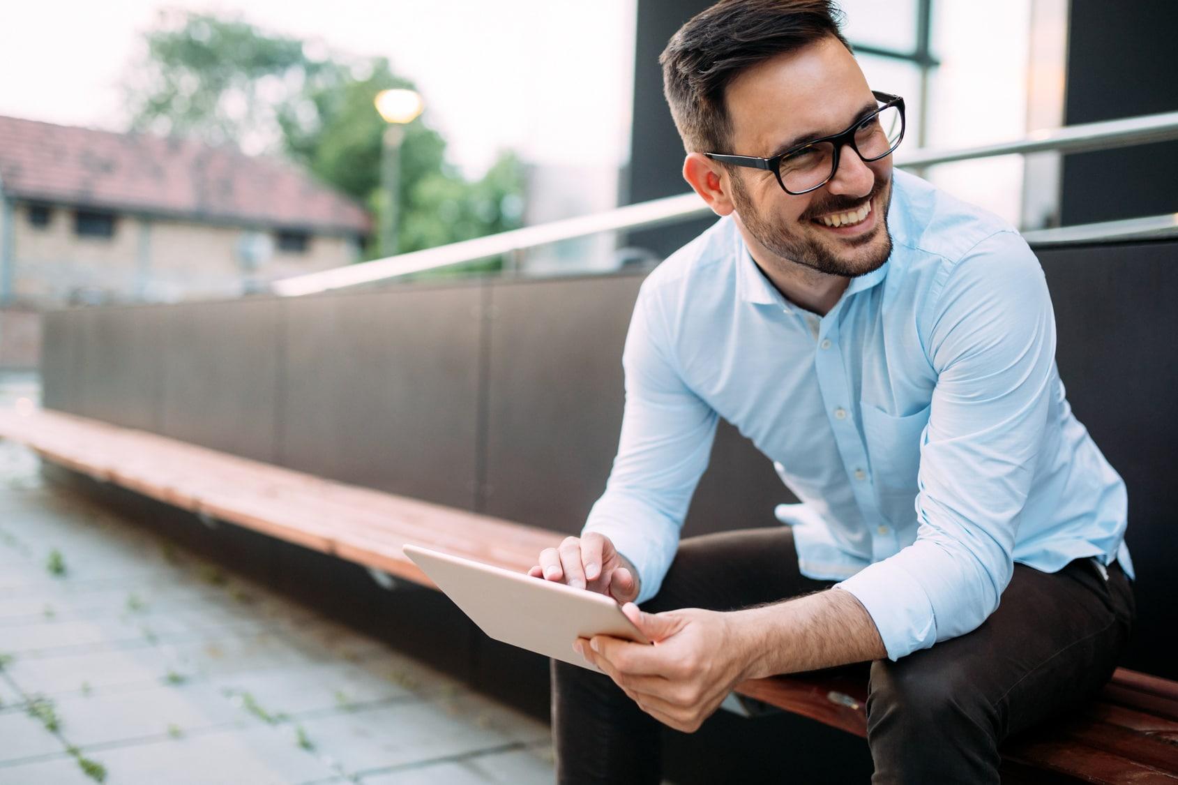 Ein junger Mann sitzt auf einer Bank an einer Universität mit einem Tablet. Er strahlt ein gutes Selbstbewusstsein durch seine Mimik aus. Er ist bekleidet mit einem hellblauen Hemd und einer schwarzen Lederhose. Er hat schwarze kurze Haare und trägt eine Brille mit schwarzen Rahmen.
