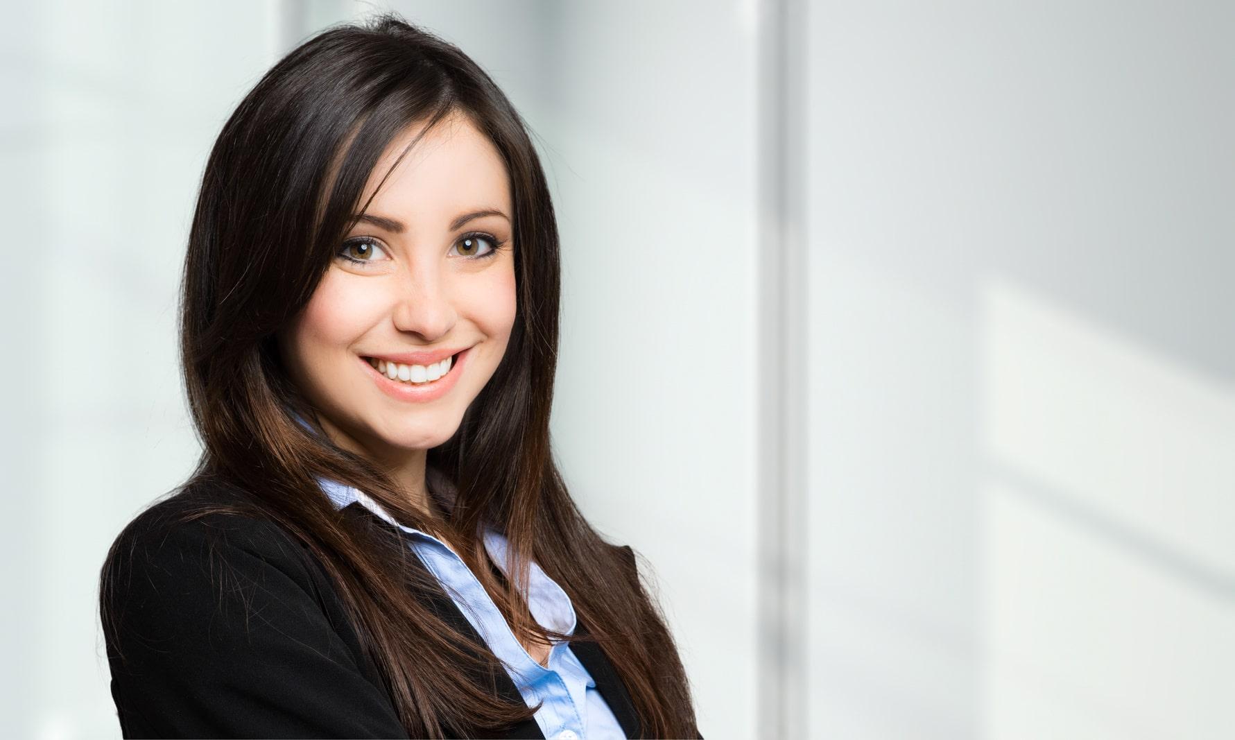 Eine junge Frau mit Schulterlangen braunen, glatten Haaren lächelt freundlich und ist sichtbar erleichtert, dass Sie mit dem Programm der unibee Institute, ihr Selbstbewusstsein stärken konnte und eine dauerhaft positive Balance spürt. Sie ist bekleidet mit einem hellblauen Hemd und einer schwarzen Jacketjacke aus Samt. Im Hintergrund ist eine weisse Tür zu sehen.