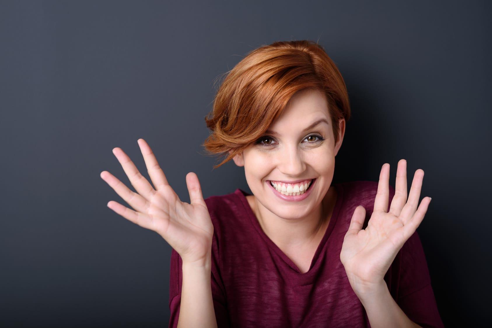 Eine Frau mit rotbraunen kurzen Haaren lächelt und hebt dabei beide Hände hoch. Sie strahlt mit Ihrer Mimik und Gestik vollstes Selbstbewusstsein aus. Sie ist bekleidet mit einem lilafarbenen Pullover. Der Hintergrund ist einfarbig dunkelblau.