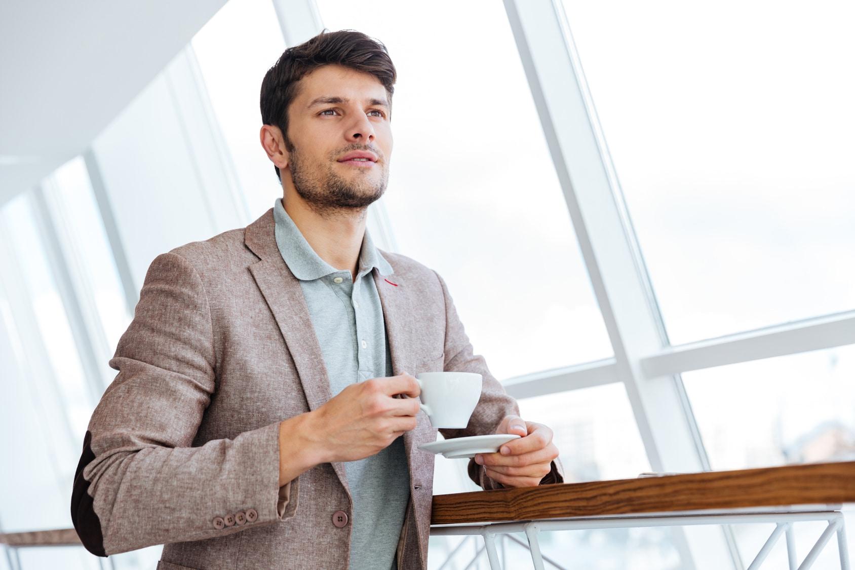 Hunger Mann steht mit einer Tasse Tee und lächelt leicht, weil er mit der Therapie gegen das Burnout Syndrom erfolgreich wieder Kraft geschöpft hat. Der Mann hat schwarze Haare und trägt eine braune Jacke.