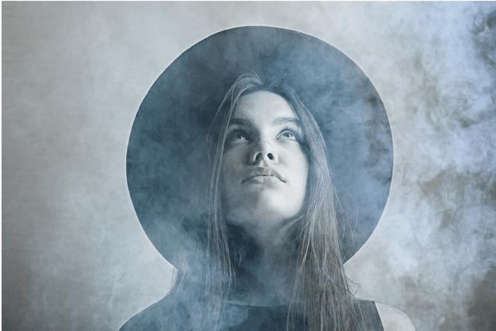 Eine junge Frau mit einem nachdenklichen Gesicht. Sie steht im Nebel und trägt einen Hut. Sie hat lange braune Haare.